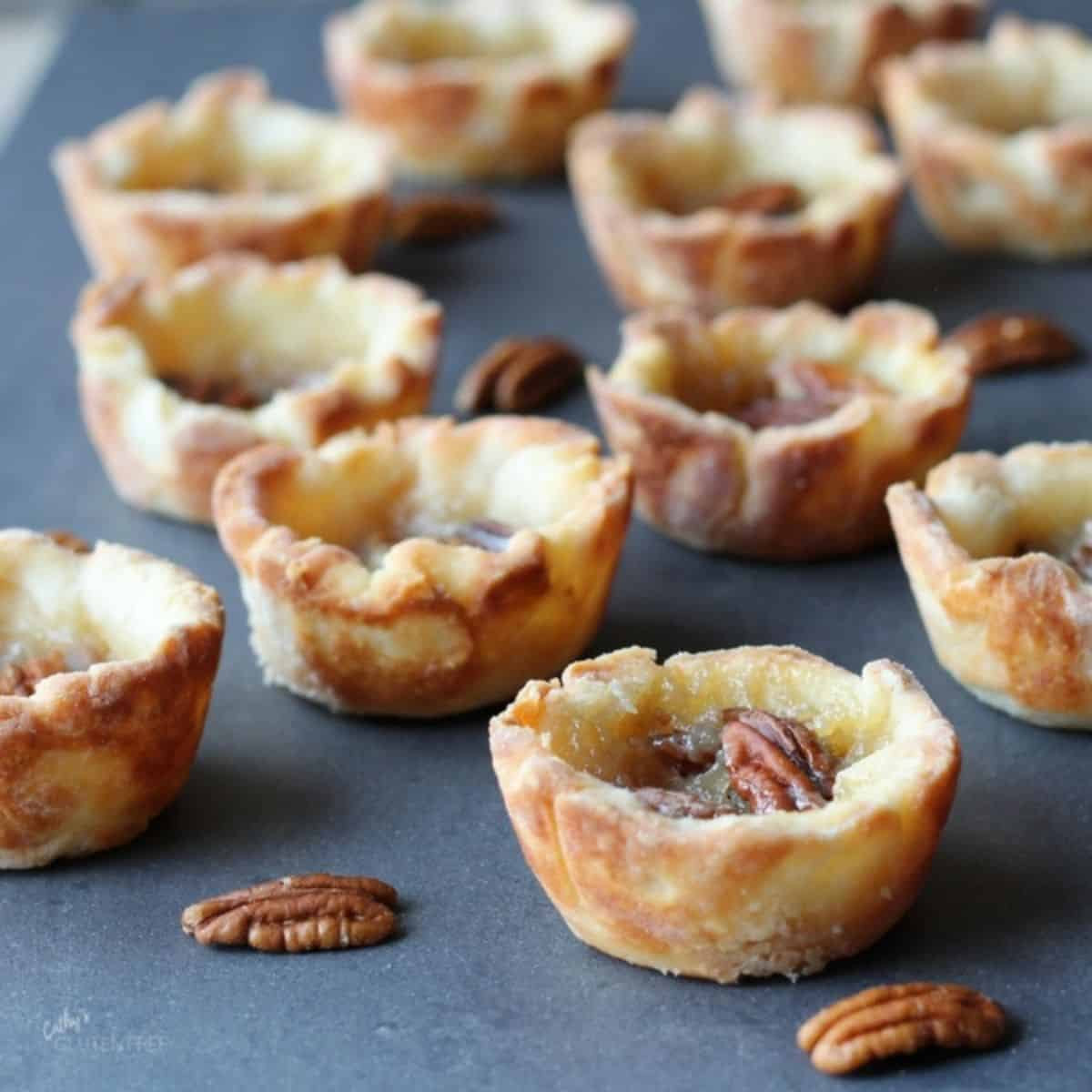 several butter tarts with pecans spread out over grey surface