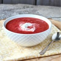 Red borscht topped with cashew yogurt in white bowl