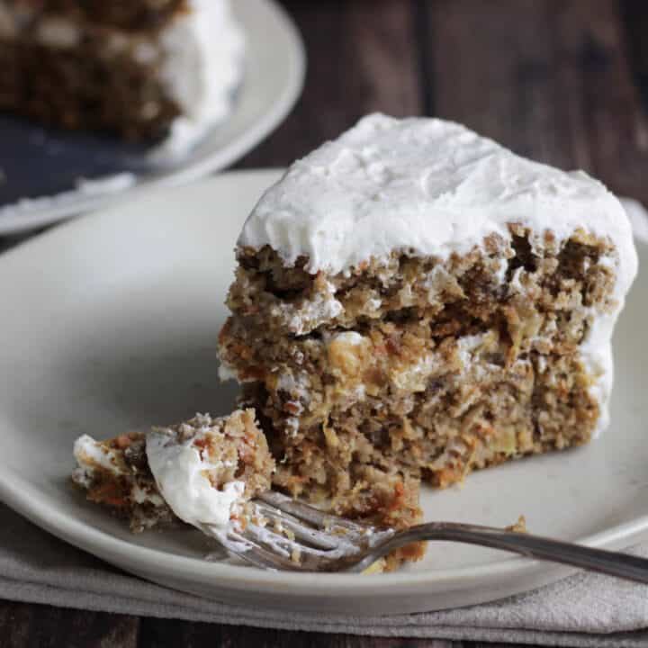wedge of carrot cake with cream cheese frosting that has a bite broken away by a fork