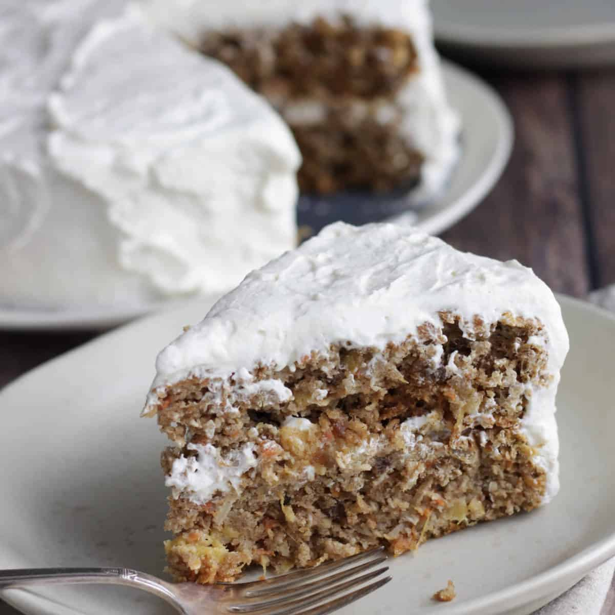 wedge of frosted carrot cake on plate with fork with remaining cake in background