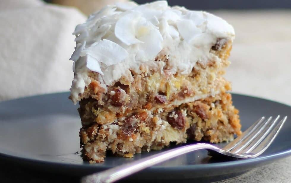 Slice of gluten free carrot cake with fluffy white frosting