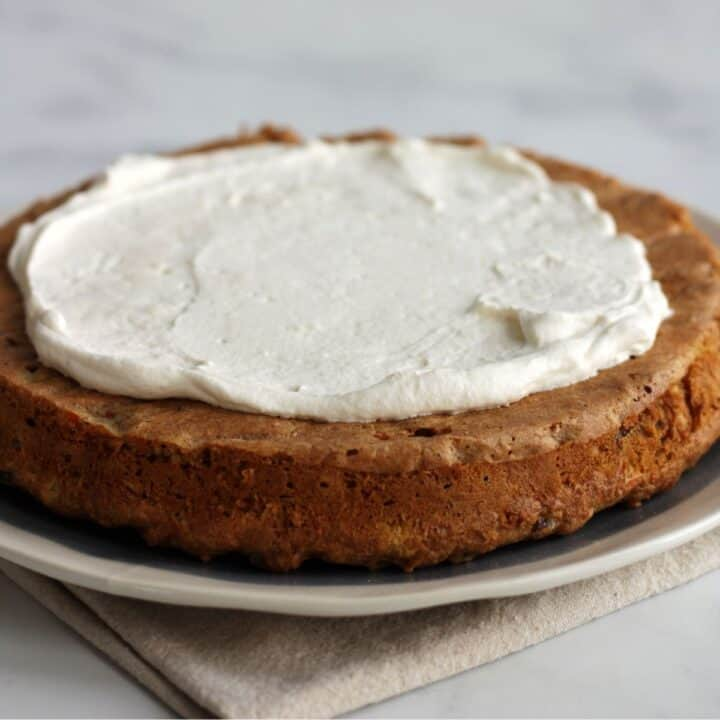 creamy white frosting is spread over a round cake layer