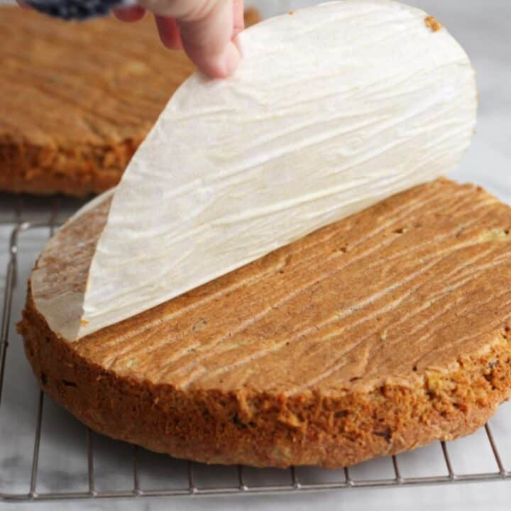 parchment paper being peeled from round cake layer on wire cooling rack