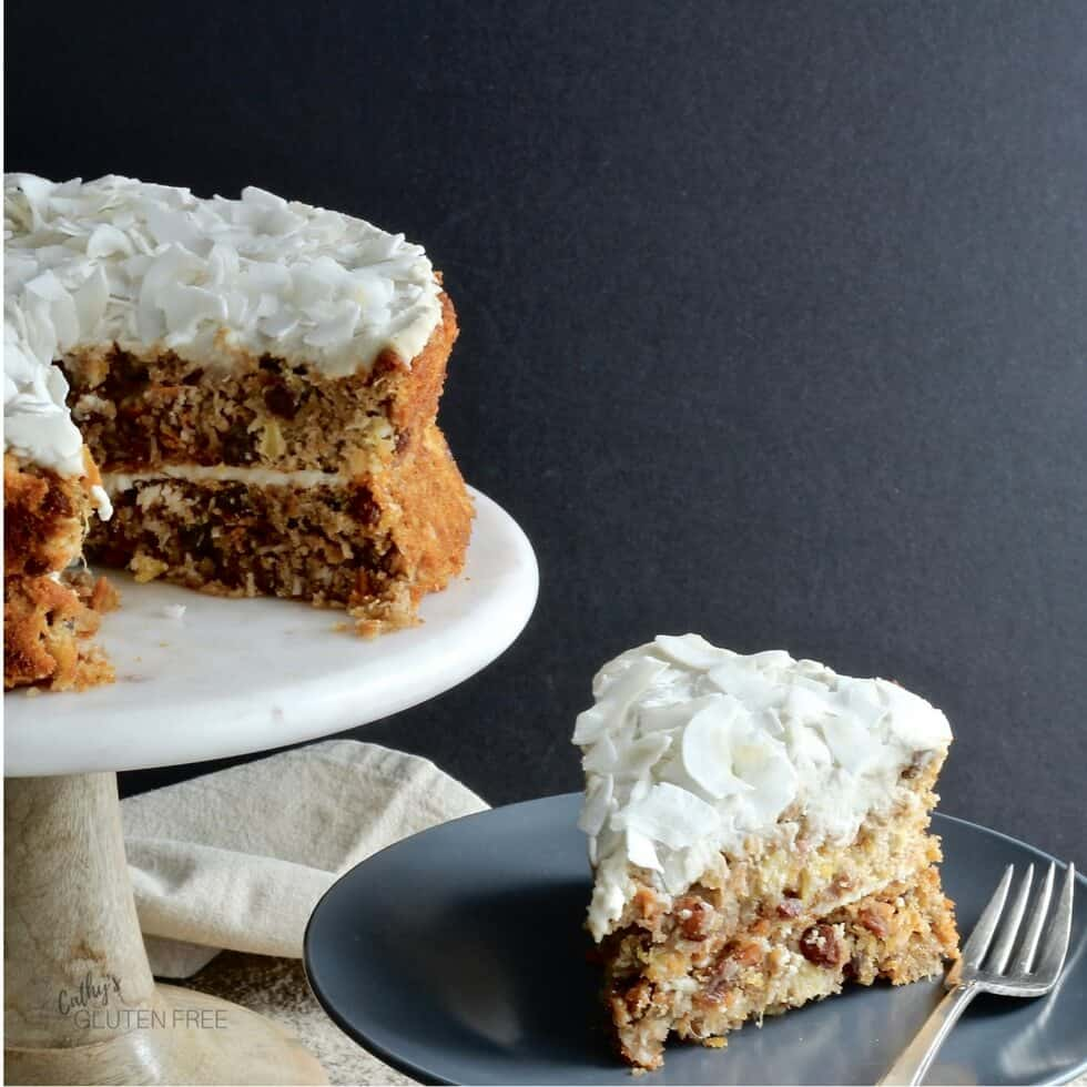 one slice of carrot cake is plated while the rest of the cake waits on a pedestal dish.