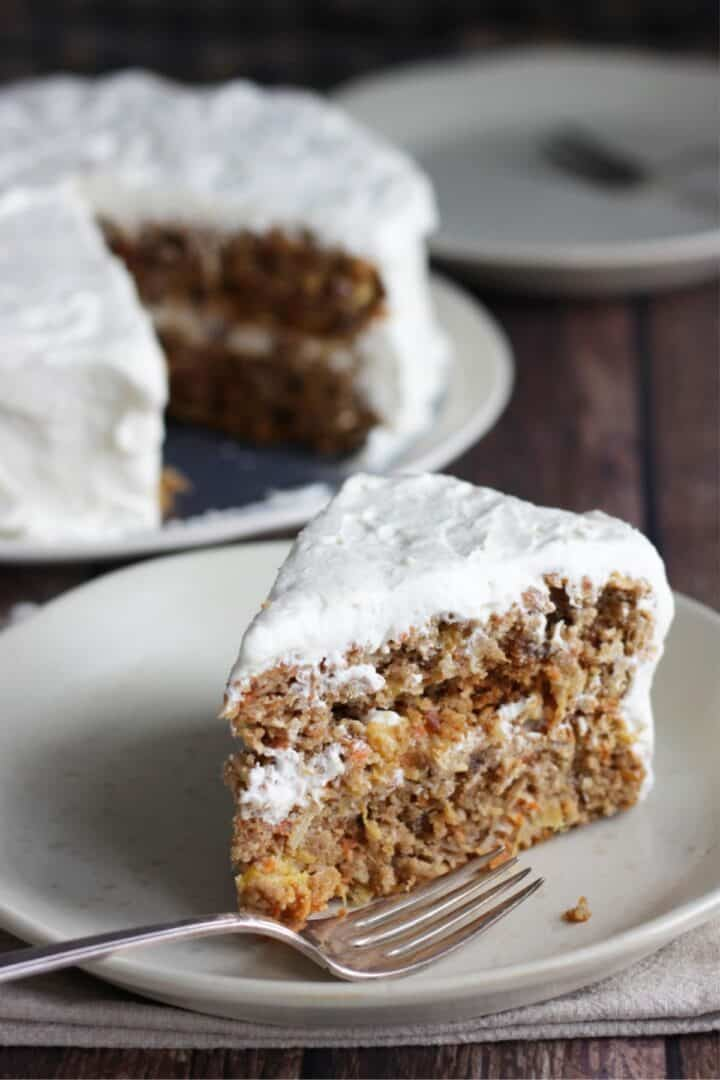 wedge of frosted carrot cake on plate with fork with remaining cake and extra plate and fork in background