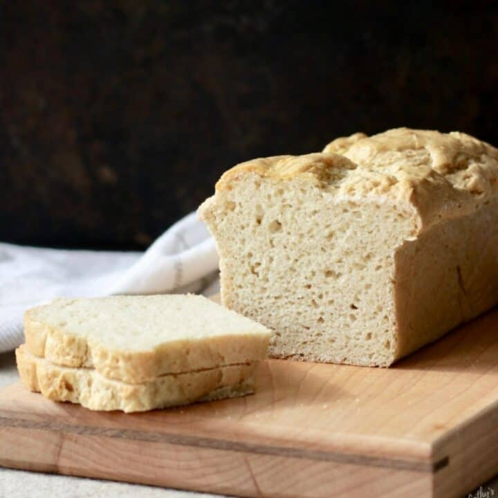 loaf of golden-crusted bread sitting on a wooden board with a couple of slices lying to the side