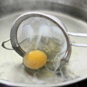 Egg Being Tipped from Strainer