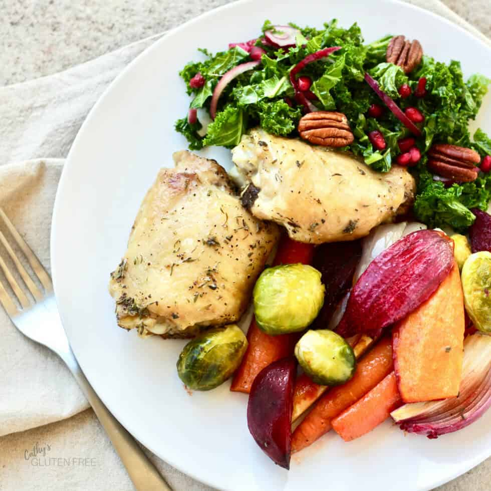 roasted chicken thighs, vegetables, and salad on a white plate
