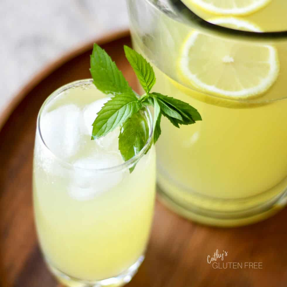 a glass of lemonade with ice and a sprig of mint sit on a wooden tray by a pitcher of lemonade
