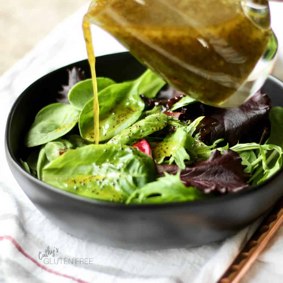 healthy homemade salad dressing poured over fresh greens