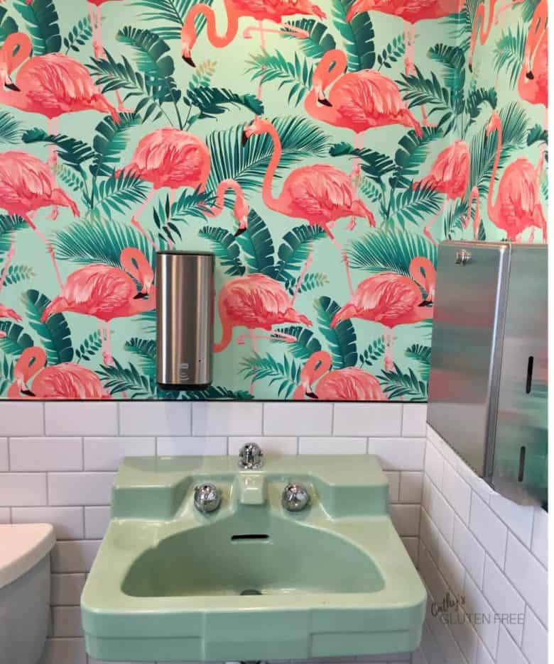 mint green sink with green and pink flamingo wallpaper above it