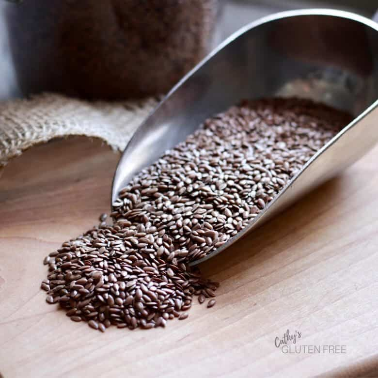 flax seeds spilling from scoop onto wooden board