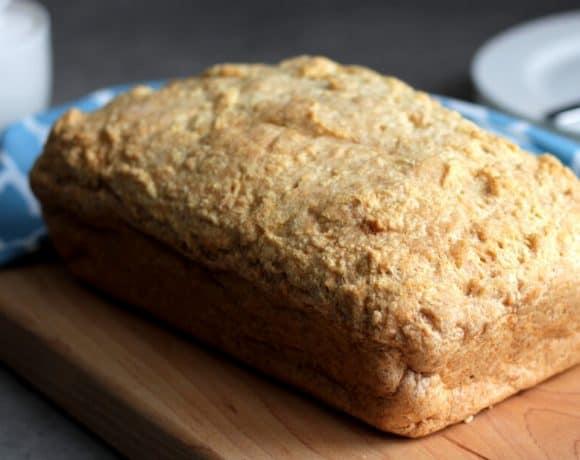 Crusty loaf of gluten free bread resting on cutting