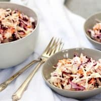 Three bowls of coleslaw with two forks