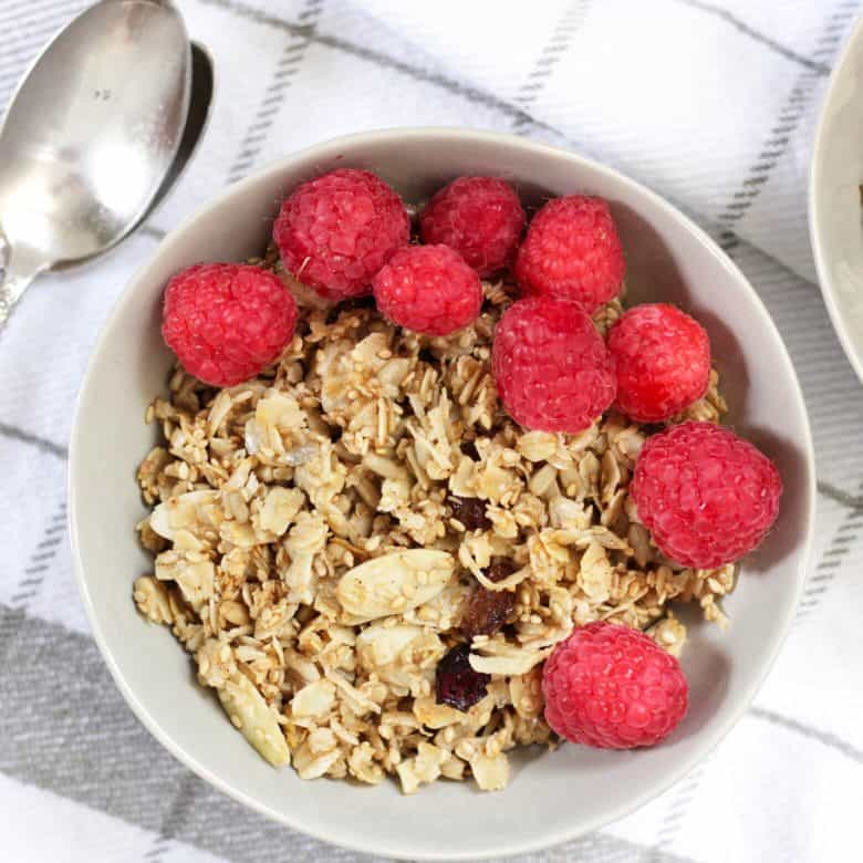looking down on a bowl of granola topped with raspberries