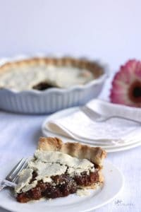 baked pie sliced and plated with white cloth napkins, pie, and pink flower in background