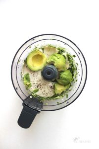avocado, cashew yogurt, and herbs in food processor bowl