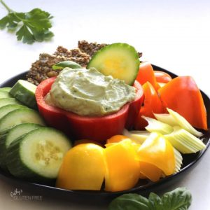 creamy dip piled inside a hollowed our half red pepper surrounded by cucumber slices, yellow pepper chunks, celery pieces, orange pepper chunks, and seed crackers