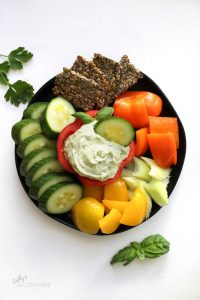 top down view of greenish creamy dip surrounded by crudites and crackers