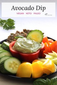 Creamy avocado dip is surrounded by chunks of fresh vegetables and crackers