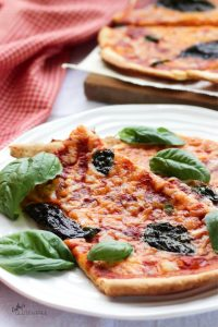 cheese and tomato-topped pizza slices garnished with basil