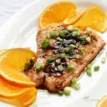 cooked salmon topped with green onion and surrounded by orange slices