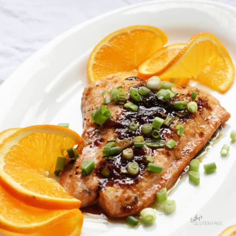 Chopped green onion tops a fillet of cooked salmon.