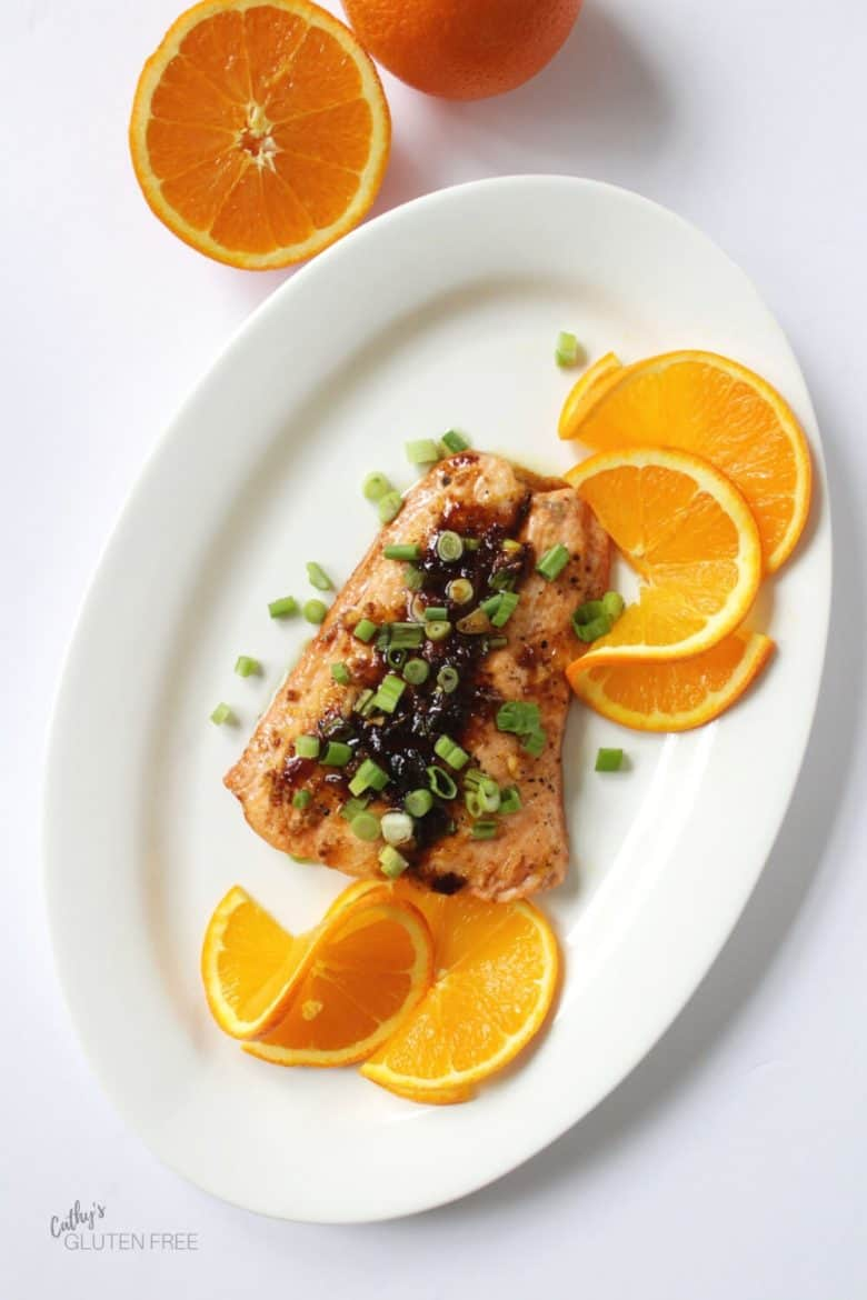 top-down view of salmon with green onion and orange slices served on an oval white platter