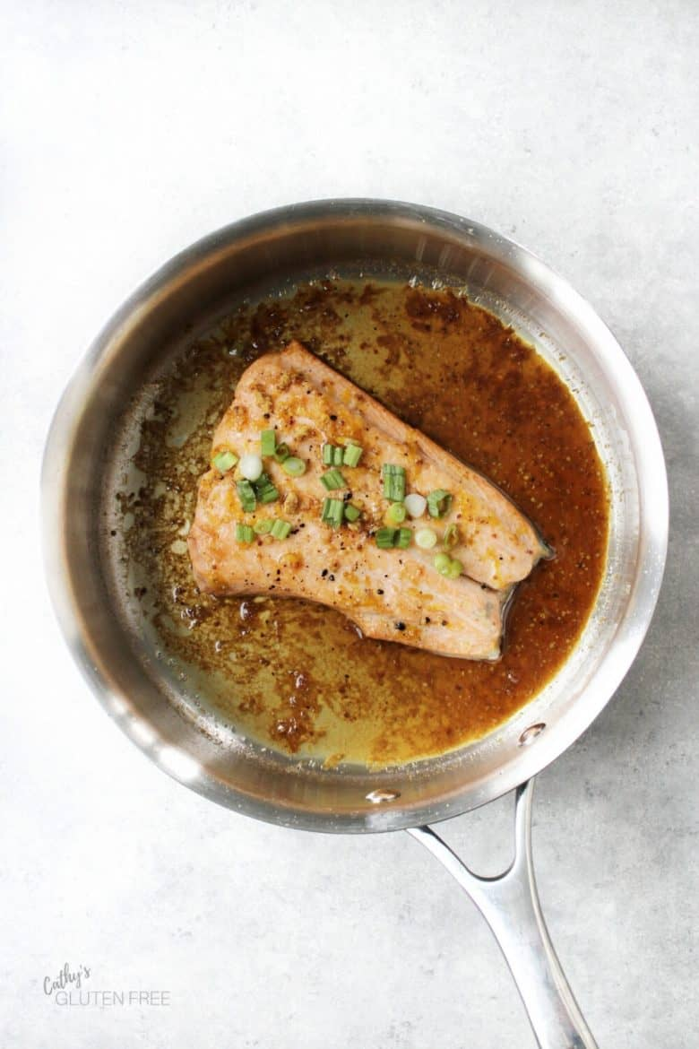 fillet of salmon sizzling in pan glaze