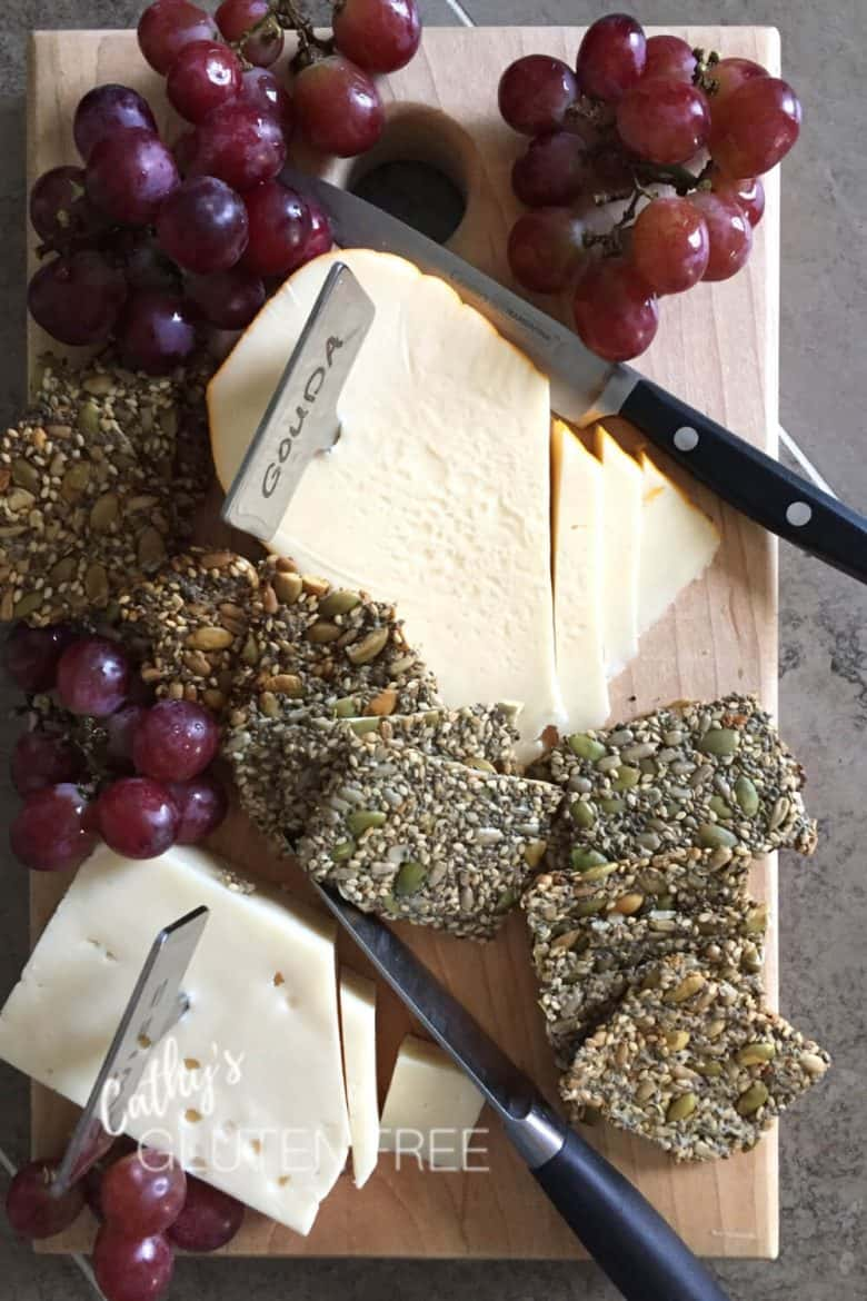 overhead view of seed crackers, grapes, and cheese on wooden board