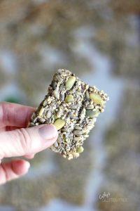single cracker with pumpkins seeds is held up between fingers