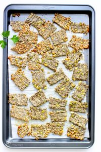 Keto 4-seed crackers spread randomly on a parchment-lined baking sheet