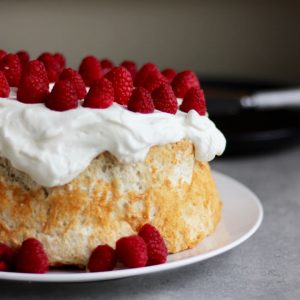 angel food cake topped with whipped cream and raspberries