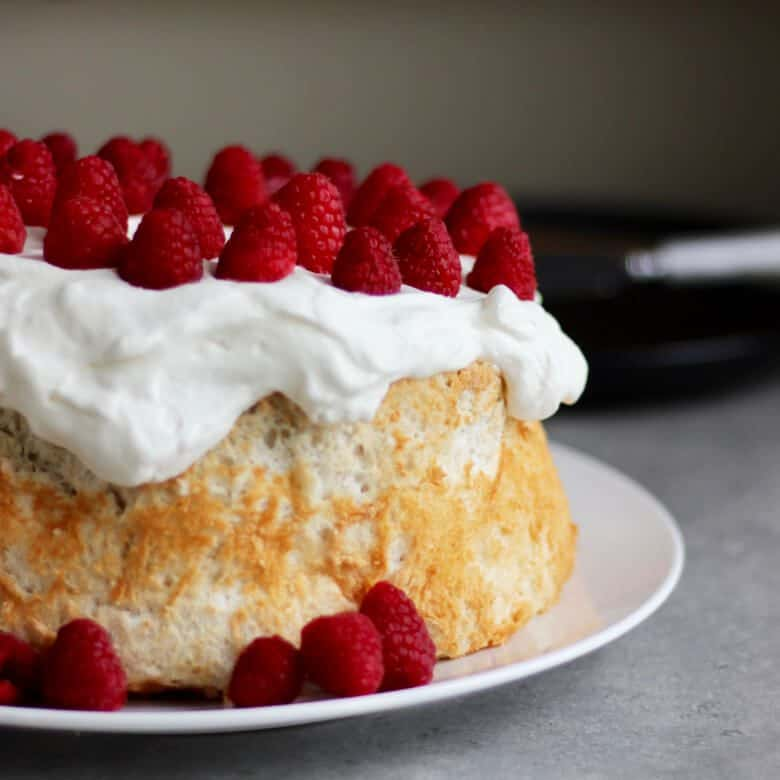 angel food cake, made with gluten free flours, topped with whipped cream and raspberries