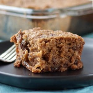 a square of moist applesauce cake sits on a dark plate with a fork beside it