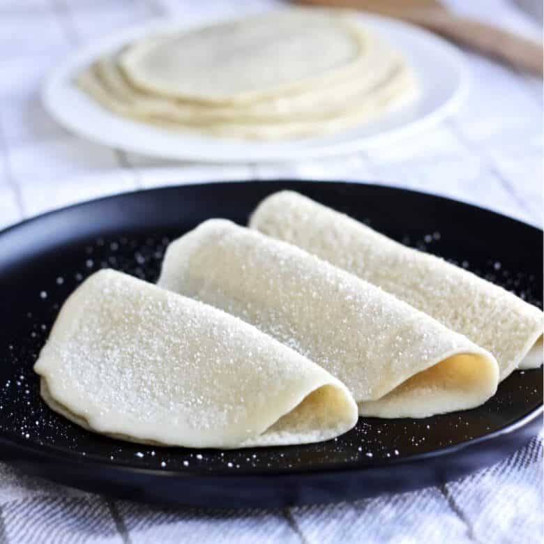 three crepes, made with gluten free flours, folded on a black plate