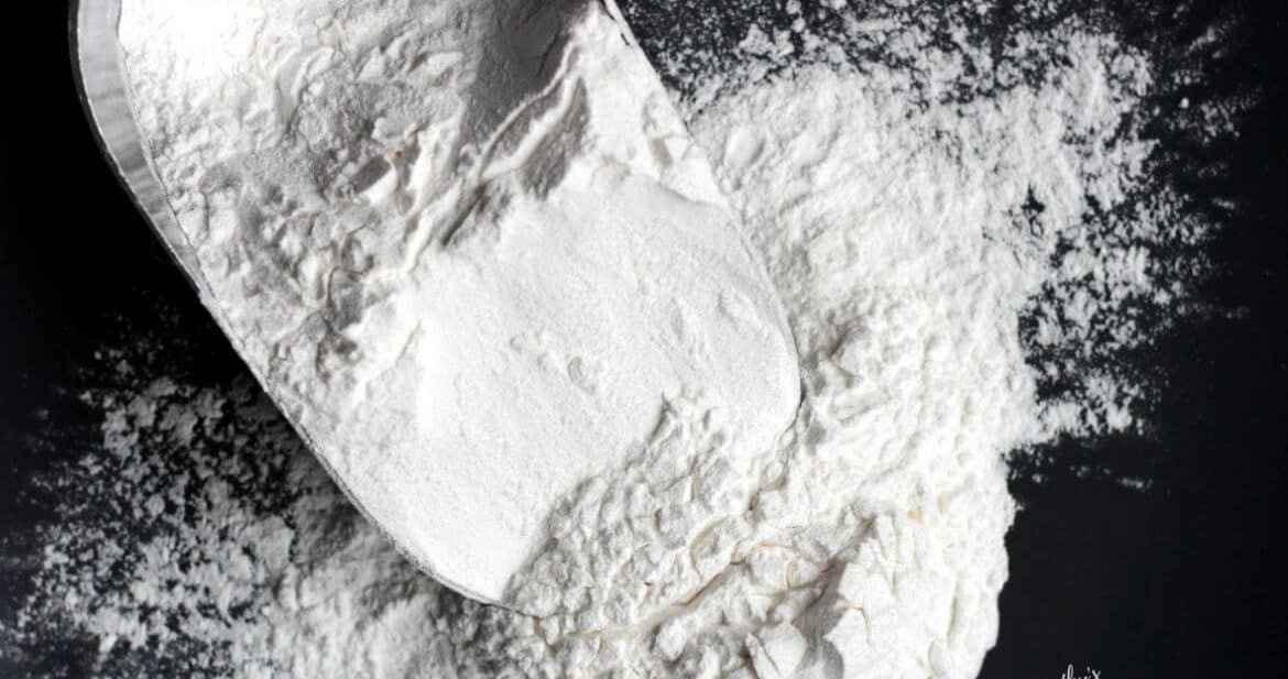 overhead shot of white flour falling from scoop on black background