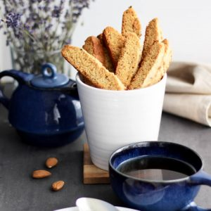 biscotti standing upright in a white cup with a cup of tea in front and lavender behind