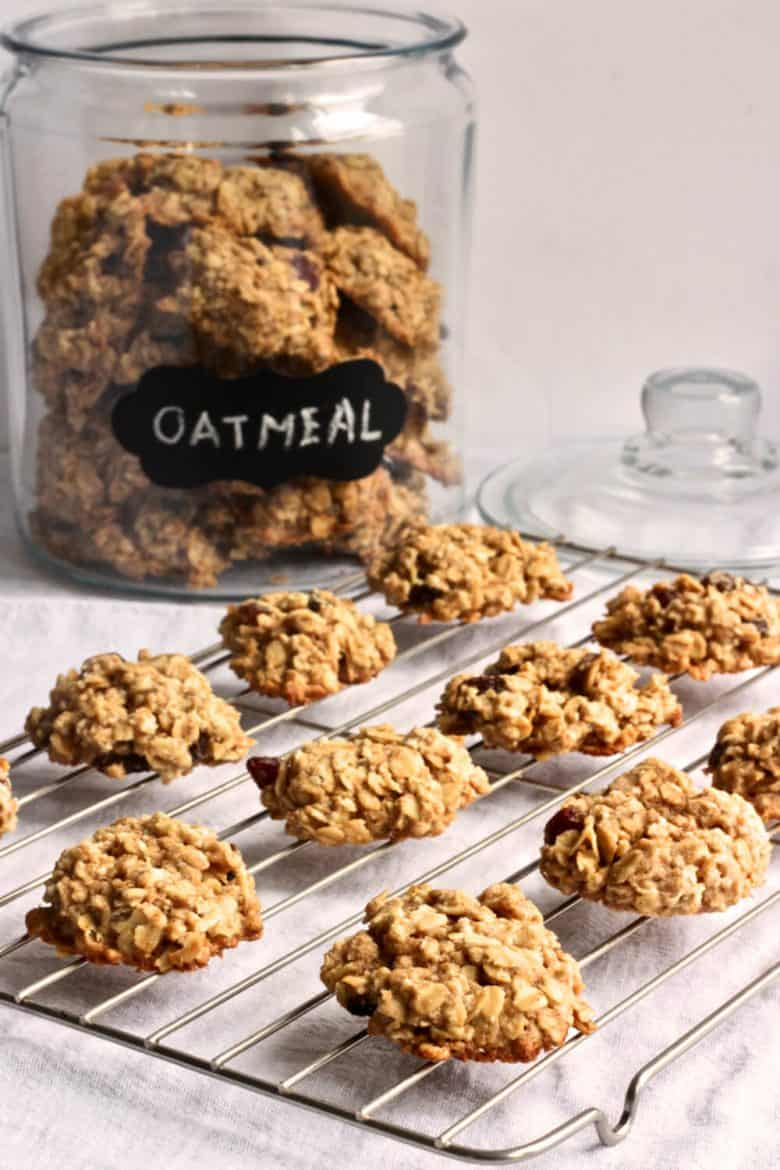 "cookies on a wire cooling rack with jar labeled ""oatmeal"" in the background"