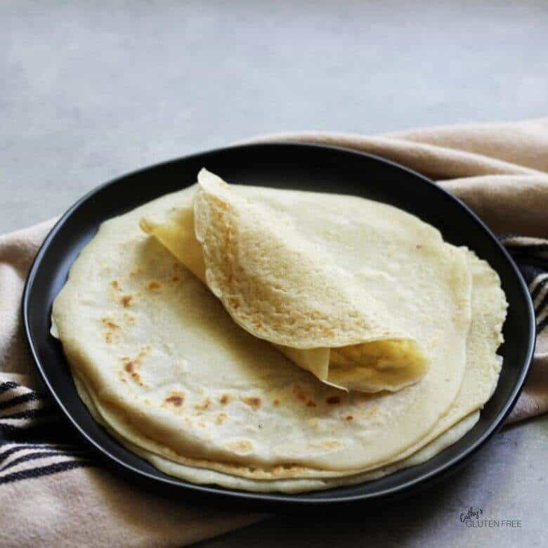 gluten free tortillas stacked on black plate