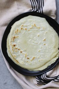 overhead view of browned tortillas on black plate