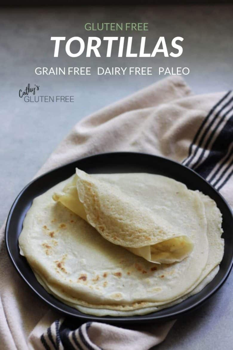 stack of grain free tortillas on black plate, with top one rolled up