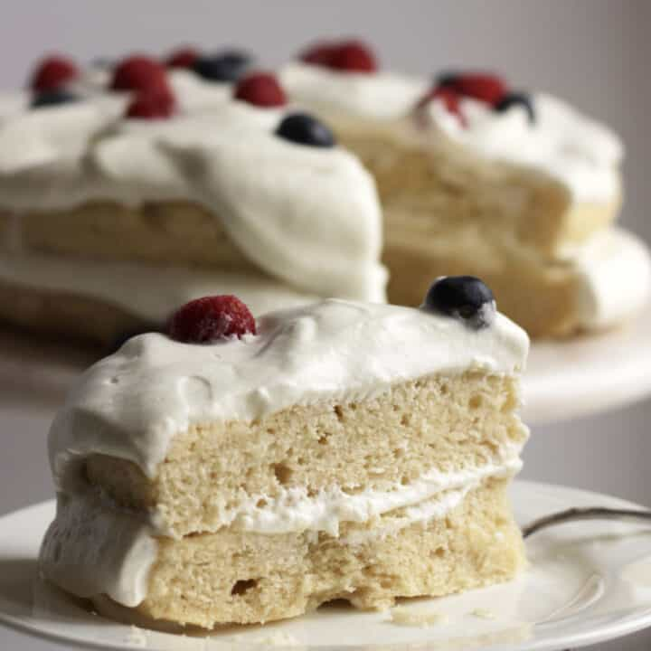 closeup of wedge of gluten free vanilla cake topped with whipped cream and berries, remaining cake in background
