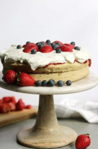 fresh blueberries and strawberries on top of the whipped cream on two layers of cake