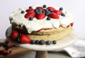 layer cake on marble pedestal topped with whipped cream and berriestal