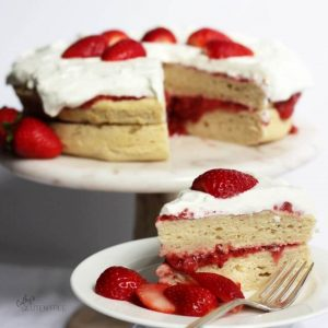 A slice of two-layer vanilla strawberry cake is served on a white plate alongside the rest of the cake.