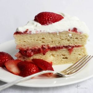 two layers of gluten free vanilla cake with strawberry jam between them and whipped cream on top, garnished with fresh strawberries
