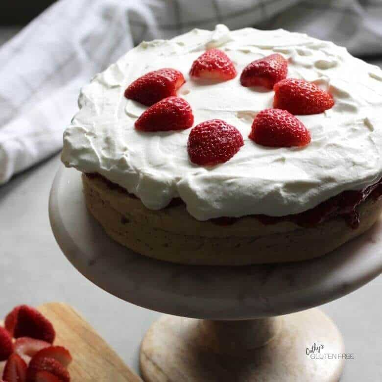 two layers of light cake with whipped cream and strawberries on top