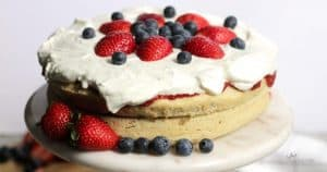 two-layers of light cake are topped with whipped cream, fresh strawberries, and blueberries