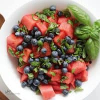 overhead view of watermelon salad with blueberries and basil